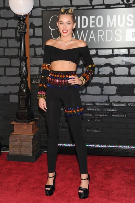 Con un peinado muy 90's y un estilismo de Dolce & Gabbana vintage, así posó Miley Cyrus ante las cámaras subida a unas maxi plataformas.